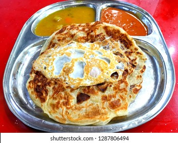 Roti telur on a plate with dal and curry.  A roti telur is a roti canai with an egg cooked inside of it.