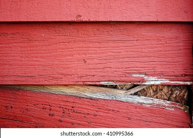 Rotted Red Clapboards Falling Apart on side of house