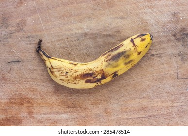 A rotten banana on a dirty mottled wooden surface