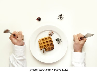 Rotten food concept. Man holding fork and knife insects and bugs eat the waffle isolated on white from top view.