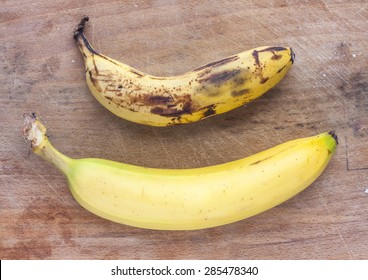 A rotten and a fresh ripe banana side by side on a mottled wooden surface