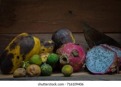 Rotten fruit on wooden background (still life)