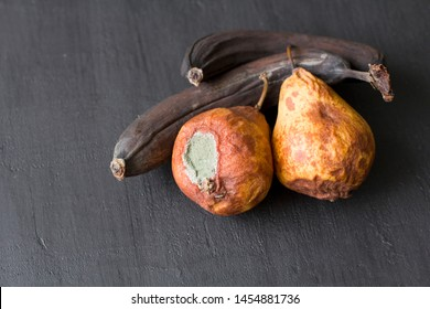 Rotten spoiled rotten fruits, bananas and pears. Black bananas on a black dark background. Damaged products, mold. Copy space for your text. Still life fruit.