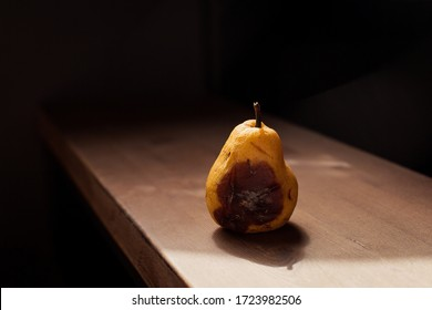 rotten spoiled yellow pear on a wooden background. spoiled overripe with mold. Unhealthy food. Garbage trash organic still life. damaged garden  harvest wormy