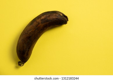 Rotten unhealthy banana resting on a yellow background