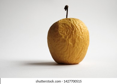 Rotten yellow apple with white background
