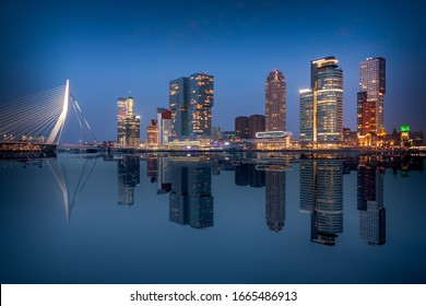 Rotterdam city skyline. Beautiful mirror reflection of the most famous buildings on the river Maas around dusk.