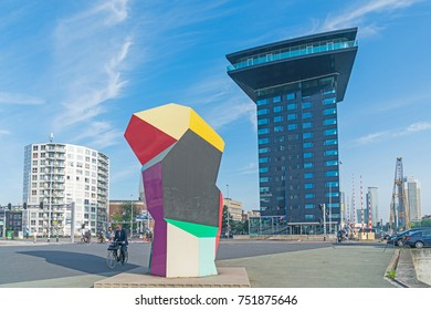 ROTTERDAM, HOLLAND -AUGUST 22; Man cycles past Marathon Image sculpture in Erasmusburg district with one of city's stunning modern architectural buildings behind August 22, 2017 Rotterdam Holland