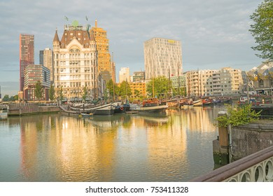 ROTTERDAM, HOLLAND- AUGUST 23, 2017;  sun rises and catches buildings across canal and shadows old style boats moored beneath the Gothic style building known as Whitehouse