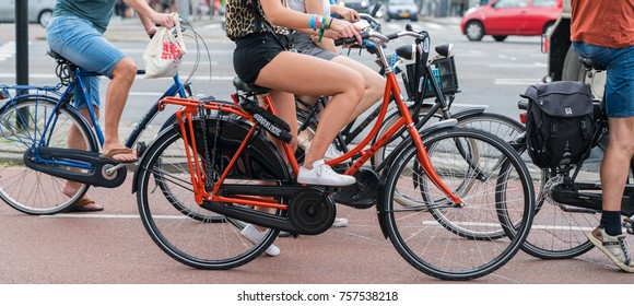 ROTTERDAM, HOLLAND - AUGUST 24, 2017; Street scene cyclists passing letterbox slot image of wheels and legs only