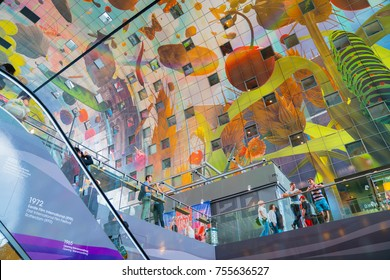 ROTTERDAM, HOLLAND - AUGUST 24; Focus on stunning Market Hall ceiling mural that arches over the entire indoor market and people on level above beside escalator August 24 2017 Rotterdam Holland