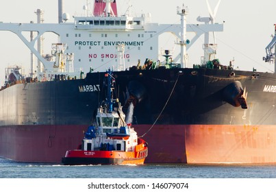 ROTTERDAM - MARCH 19: Tugboats asisting the supertanker 'Marbat' on March 19, 2012 in Rotterdam, Holland. The 'Marbat' (320,000 dwt) is the first of a new series of very large crude carriers (VLCC)
