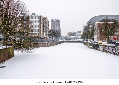 Rotterdam, March 3, 2018: view across frozen and snow-covered Steigersgracht canal towards Markthal and public library