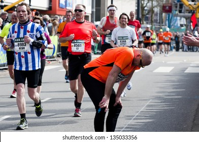 ROTTERDAM, THE NETHERLANDS - APRIL 14 : Exhausted runner giving up during the Annual Fortis Rotterdam Marathon. Runners on the city streets on April 14, 2013 in Rotterdam, The Netherlands.