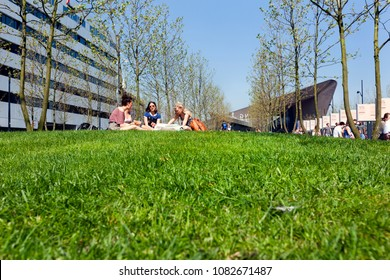 Rotterdam, The Netherlands - April 20,  2018 : Four young women sitting on the grass in front of the central station in Rotterdam with other people in the background