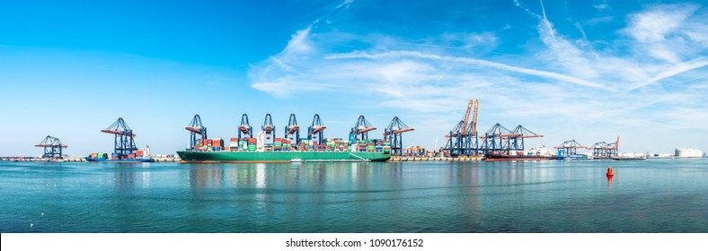 ROTTERDAM / NETHERLANDS - APRIL 20 2018 : Large harbor cranes loading container ships in the port of Rotterdam.