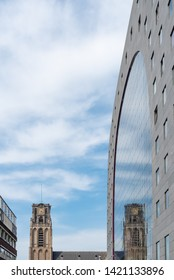 Rotterdam, Netherlands - April 23, 2019 : Saint Lawrence church reflecting on the Markthal building facade against sky