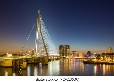 ROTTERDAM, NETHERLANDS - APRIL 6: Skyline of city at dusk, with the Erasmus Bridge illuminated in the blue hour at dusk, reflections in the river water, on April 6, 2015, in Rotterdam, Netherlands,