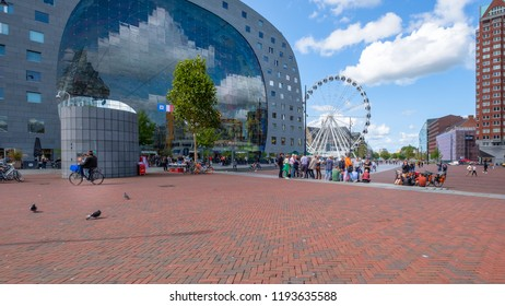 ROTTERDAM, THE NETHERLANDS - AUG 30, 2018 : View of the outside of the market hall in Rotterdam with a large Ferris wheel and groups of people and cyclists at the square in front of the building.