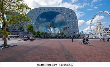 ROTTERDAM, NETHERLANDS - AUG 30, 2018 : Look through with nice reflections in the glass of the market hall in Rotterdam. A Ferris wheel next to the building and many people and cyclists on the square.