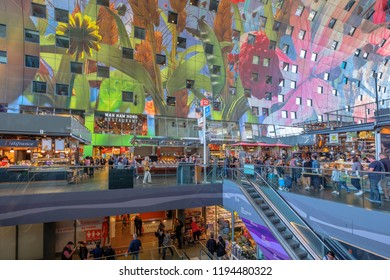 ROTTERDAM, THE NETHERLANDS - AUG 30, 2018 : Shopping people at the escalator, under the arch with apartments and offices, inside the beautiful artistic market hall of Rotterdam, the Netherlands.