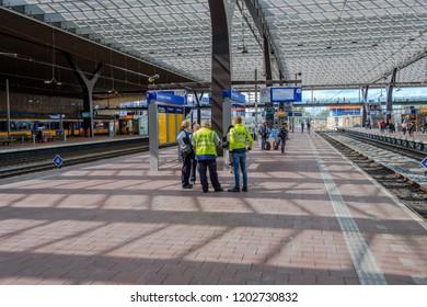 ROTTERDAM, THE NETHERLANDS - AUG 30, 2018 : Employees of the Dutch railways assist  a passenger on a platform in the Central Station in Rotterdam, the Netherlands.