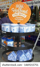 ROTTERDAM, NETHERLANDS - August 2, 2019. Typical Dutch syrup waffles, Goudse stroopwafels, from Holland in blue white windmill boxes and miniature canal houses in Delft blue style, Markthal market.
