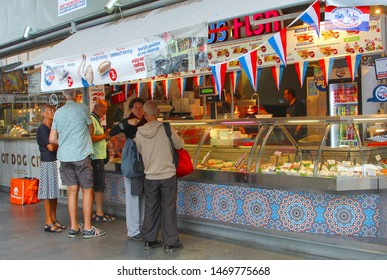 ROTTERDAM, NETHERLANDS - August 2, 2019. People are buying typical Dutch sandwiches with herring and man sells sea food in store with Holland flags in famous Markthal, famous market hall at Blaak.