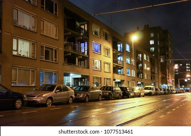 Rotterdam, The Netherlands - December 10, 2011: Parked cars along apartment blocks and a road by night in the city center