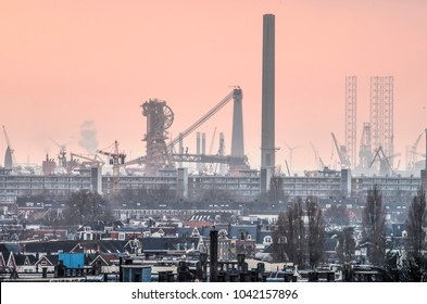 Rotterdam, The Netherlands, February 5, 2018: Giant chimneys, cranes and other industrial equipment in the western port areas in Rotterdam are towering above the adjacent neighbourhoods