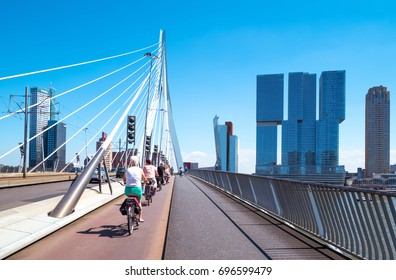 Rotterdam, The Netherlands - July 18, 2016:  Cyclists crossing the Erasmus bridge on the Maas river with the De Rotterdam towers in the background