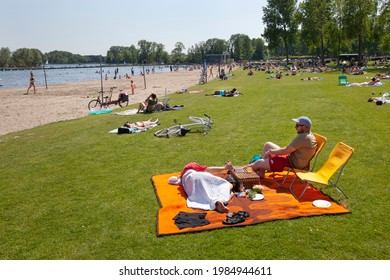 Rotterdam, Netherlands – June 2, 2021: People having fun on the beach and in water of the Kralingse Plas in Rotterdam