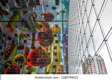 Rotterdam, The Netherlands, June 20, 2015: Looking up to the colorful artwork on the ceiling and the innovative steel cable supported glass facade in the Markthal by MVRDV architects