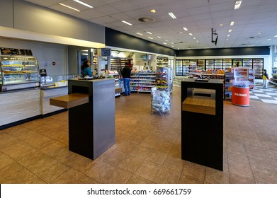 Rotterdam, Netherlands, June 2017. Inside the service shop of a petrol station, with three customers and displays with food, drink and snacks
