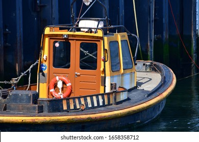 Rotterdam, The Netherlands -June 2019: Small weathered former tug boat moored in the harbor against the steel structure of a quay in Rotterdam