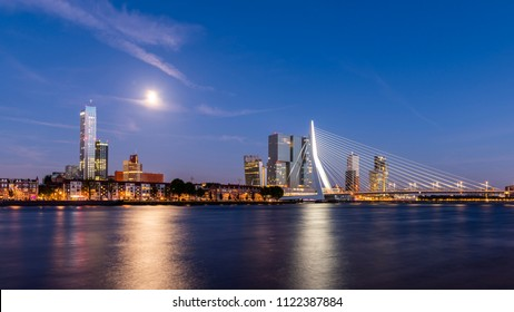 Rotterdam, Netherlands - June 26, 2018: Rotterdam at the river Nieuwe Maas during nighttime with full moon and the Erasmusbrug.
