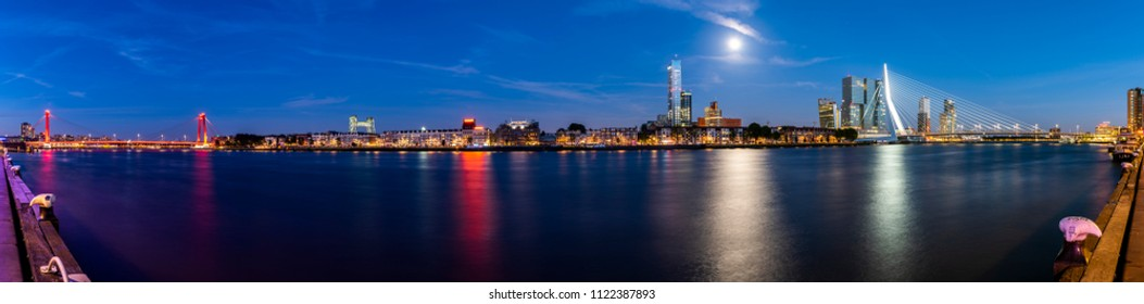 Rotterdam, Netherlands - June 26, 2018: Panoramic view of Rotterdam at the river Nieuwe Maas during nighttime with full moon, the Willembrug and the Erasmusbrug.