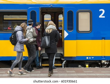 Rotterdam, The Netherlands - March 10, 2017: Travelers at the platform near the door of a train in railway station Rotterdam in the Netherlands.