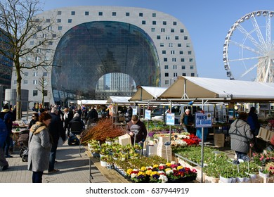 ROTTERDAM, THE NETHERLANDS - MARCH 2016: Marketplace in Rotterdam with flower stall and people shopping and in the background a ferris wheel and the architectural masterpiece 'Markthal'