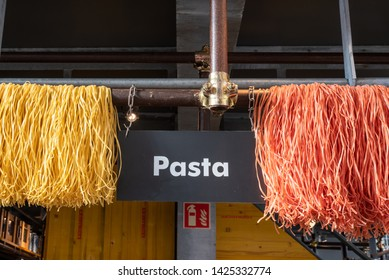 Rotterdam, Netherlands - May 2, 2019: Yellow and red pasta hanging in a store in the markthal famous covered market