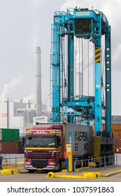 ROTTERDAM, NETHERLANDS - SEP 6, 2013: Straddle carrier placing a shipping container on a truck trailer in a terminal of the Port of Rotterdam.