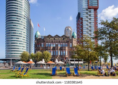Rotterdam, Netherlands – September 18, 2018: Reading a book in a beach chair in front of the famous Hotel New York in Rotterdam