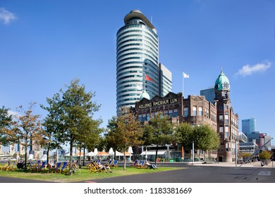 Rotterdam, Netherlands – September 18, 2018: Sunbathing in a beach chair in front of the famous Hotel New York on the south bank in Rotterdam