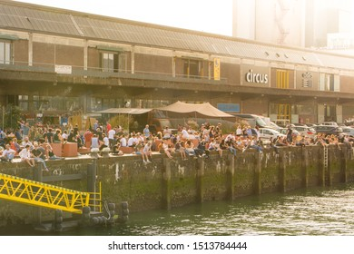 Rotterdam, Netherlands, September 2019: people relaxing and enjoying the sun on the quay of Kattendrecht, in front of Fenix Food Factory in Rotterdam.