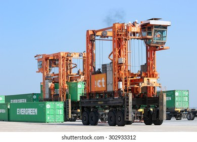ROTTERDAM, NETHERLANDS - SEPTEMBER 8, 2013: Straddle carrier moving a shipping container in the Port of Rotterdam. The port is the largest in Europe and facilitate the needs of a hinterland with 40,000,000 consumers.