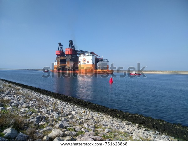 ROTTERDAM SEAPORT - SEPT 15, 2017:  Hermod semi-submersible crane vessel (SSCV) loaded on the Dockwise Vanguard heavy load carrier outbound on its final route to be demolished in China