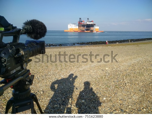 ROTTERDAM SEAPORT - SEPT 15, 2017: dropshadow of a camera crew capturing shots of special marine transport, Hermod semi-submersible crane vessel (SSCV) loaded on Dockwise Vanguard heavy load carrier