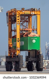 ROTTERDAM - SEP 6, 2015: Straddle carrier moving a cargo container in a shipping terminal in the Port of Rotterdam.