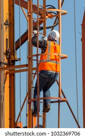 ROTTERDAM - SEP 8, 2012: Worker climping up a straddle carrier in a shipping terminal in the Port of Rotterdam.