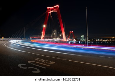 Rotterdam Willemsbrug at night.  Fast traffic lighttrails at the city center side of the Willemsbrug in Rotterdam, the Netherlands. Light trails of cars and buses.